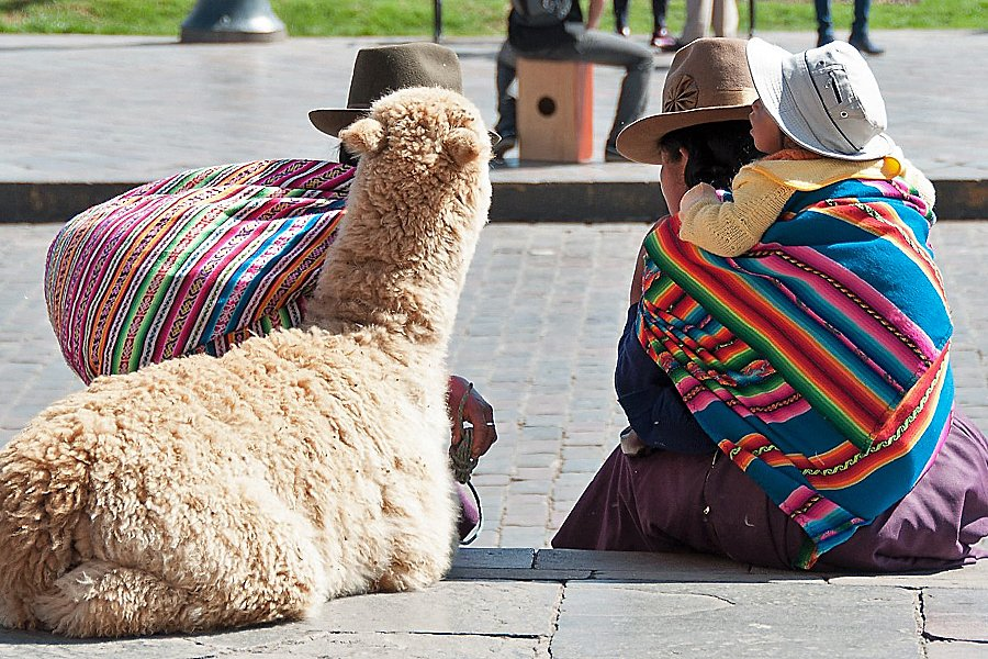 Two women in brightly coloured shawls chatting