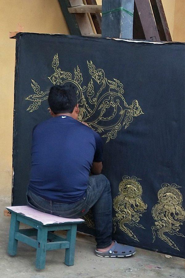 Man dressed in navy blue paintsan intricate godlen dragon on black cloth